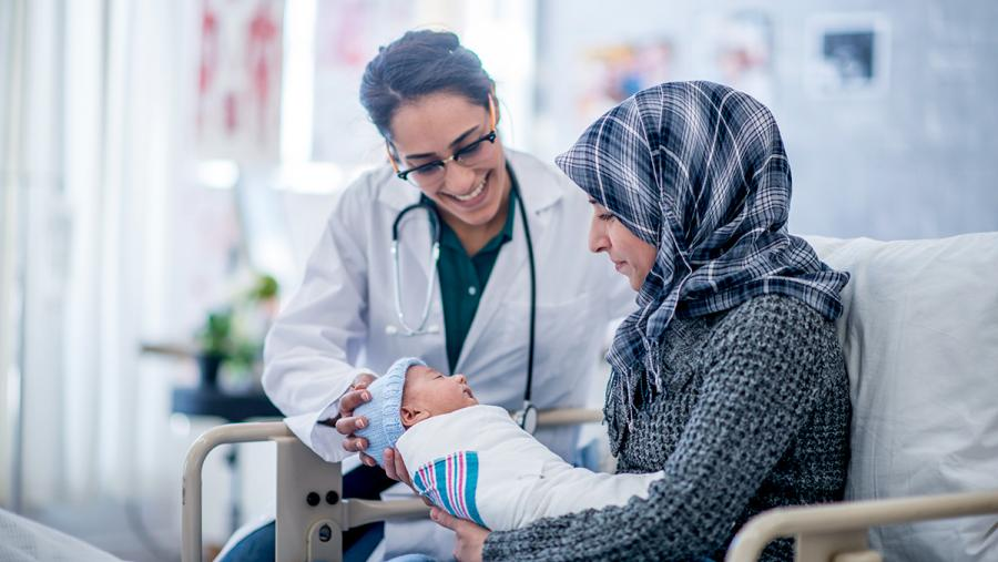 Image of two women seating, one a doctor with white coat and stethoscope and a the other holding a new born baby boy.