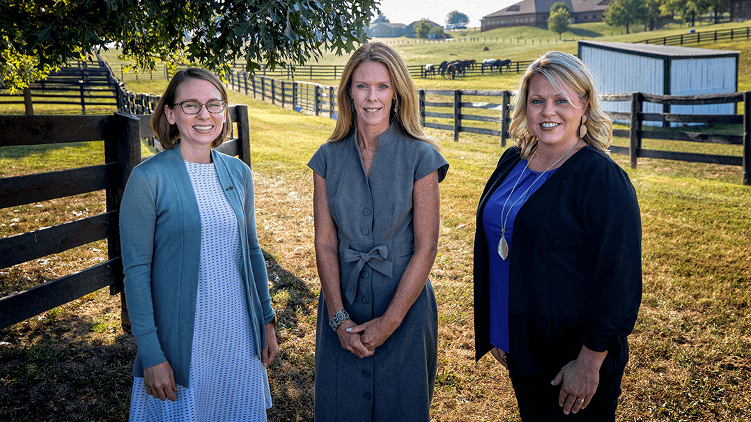 Three women stand next to each other in front of a fence at a horse farm.
